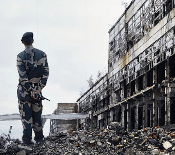 Soldier standing atop the ruins of a building surveys the war-wracked landscape in Donbass. Source: Harriman.