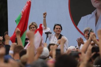Sviatlana Tsikhanouskaya with her hand raised while campaigning as a Belarusian presidential candidate at a rally in Minsk, 19 July 2020. Photo: tut.by
