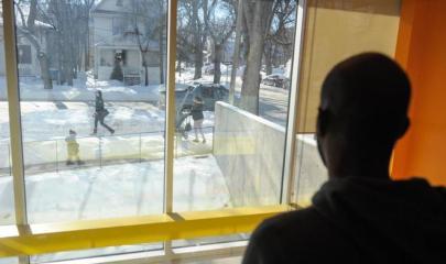 un inmigrante procedente de Yibuti mira por la ventana en un centro de refugiados en Manitoba/ AFP