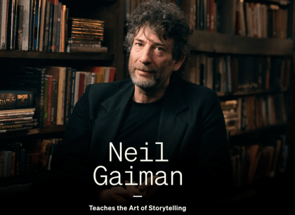 Neil Gaiman in front of a bookcase