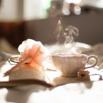 teacup on book beside pink flower decor