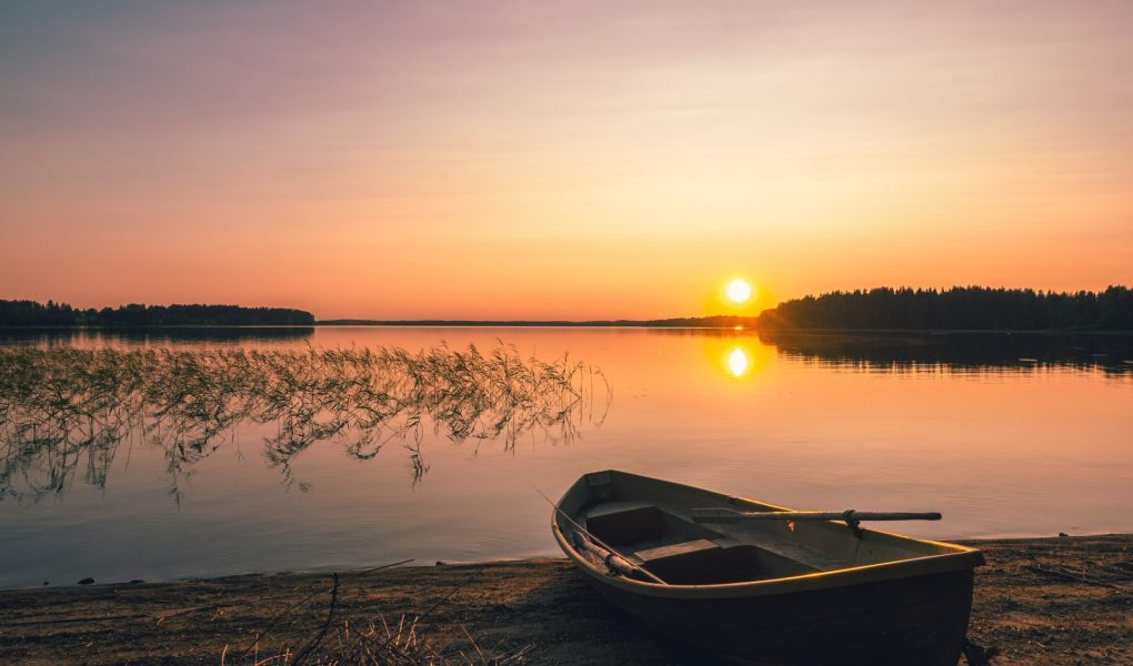 rowboat pulled up onto the beach at sunset over the lake