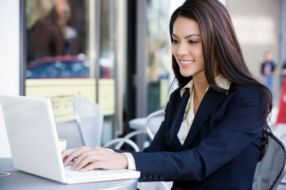 Mujer-sonriente-leyendo-un-email-en-su-portatil-en-la-mesa-de-su-oficina