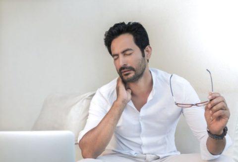 Muž držící se za bolestivou šíji