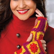 Woman in a red coat wearing fingerless gloves in red, orange, and magenta