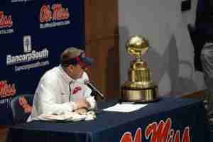 Coach Freeze takes a look at the Egg Bowl trophy after his Rebels defeated State, 31-17. (Photo credit: Mike Bedgood)