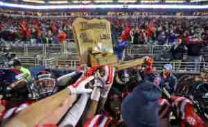 Ole Miss players celebrate their win by hoisting the Magnolia Bowl Trophy. (Photo credit: Josh McCoy, Ole Miss Athletics)