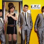 le groupe marcel et son orchestre - un membre en fille avec une belle robe noir sortant des toilettes homme, entouré par les autres membres en costard cravate léopard