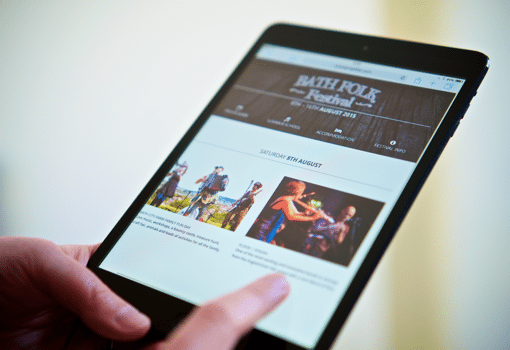 Hands browsing a festival website on an iPad