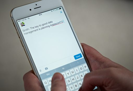 Hands typing a tweet using an iPhone