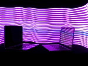Two laptops with lights in background