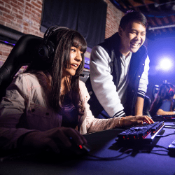 Two people staring at a computer monitor playing video games