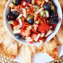 A bowl of fruit salsa arranged in the middle of a plate of cinnamon chips.