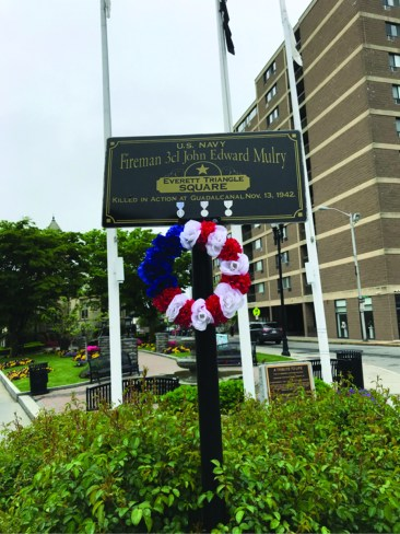 A wreath is placed on a sign in an empty Everett Square.