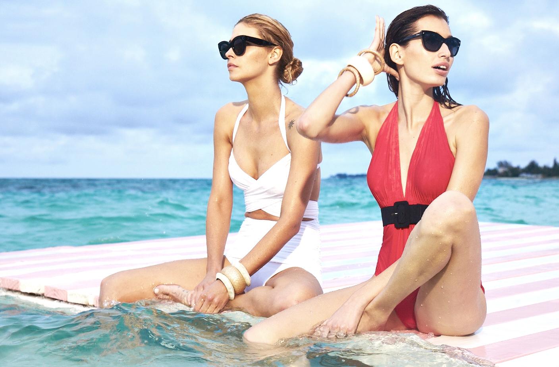 Two women sit on diving platform in ocean