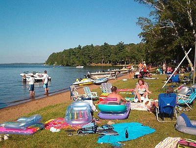 People at the beach at Evergreen Lodge on Woman Lake Longgille Minnesota