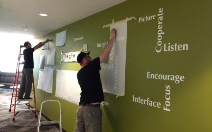 Getting the measurements and placement just right before laying down cut vinyl letters per our customer's vision.