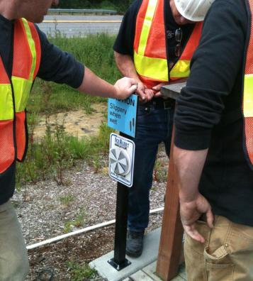 The installation crew works to secure small sign stands securely into place throughout a full property installation.