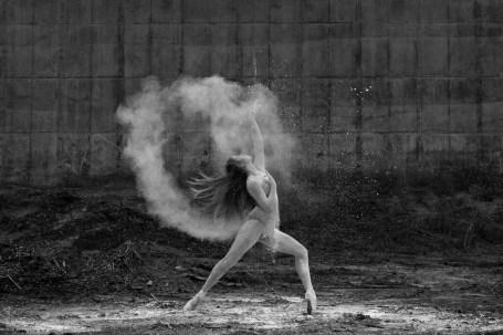 Female ballet dancer strikes a pose within a powdery circle