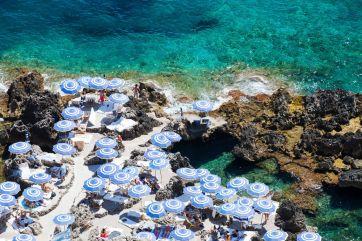 Beach umbrellas on the coastline of Capri, Italy