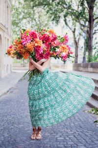 Woman holding a large bouquet of pink and orange flowers