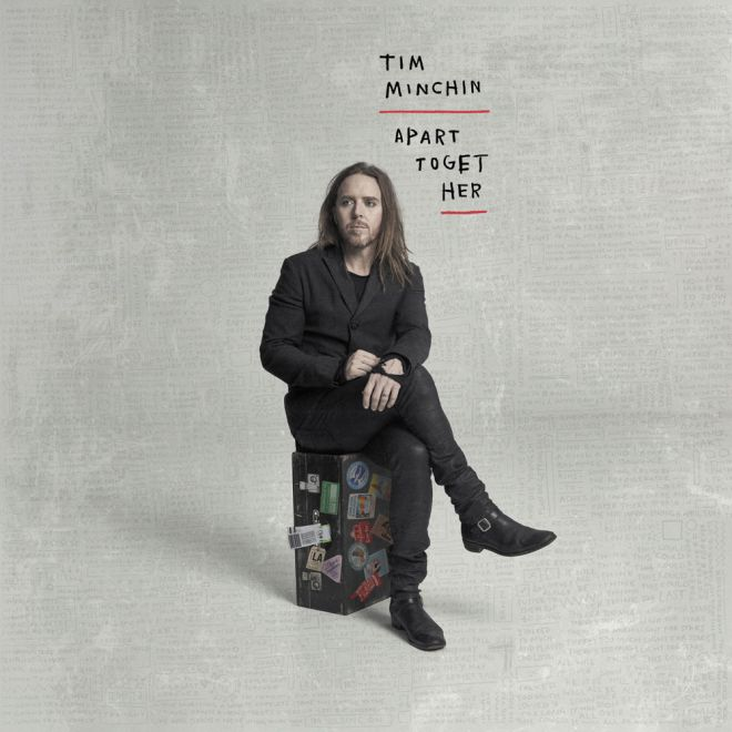 apart together album cover, tim minchin sitting on a suitcase wearing a suit