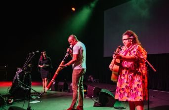 Astrid, Waveney and a special guest holding a didgeridoo stand on stage