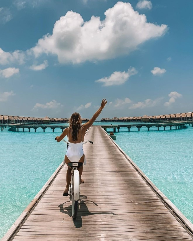 travel a little luxe and Danielle Greentree photography : Danielle riding a bicycle along a boardwalk surrunded by crystal-clear sea water and bungalows in the distance