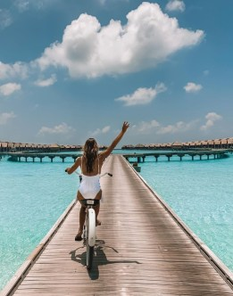 travel_a_little_luxe : Danielle riding a bicycle along a boardwalk surrunded by crystal-clear sea water and bungalows in the distance