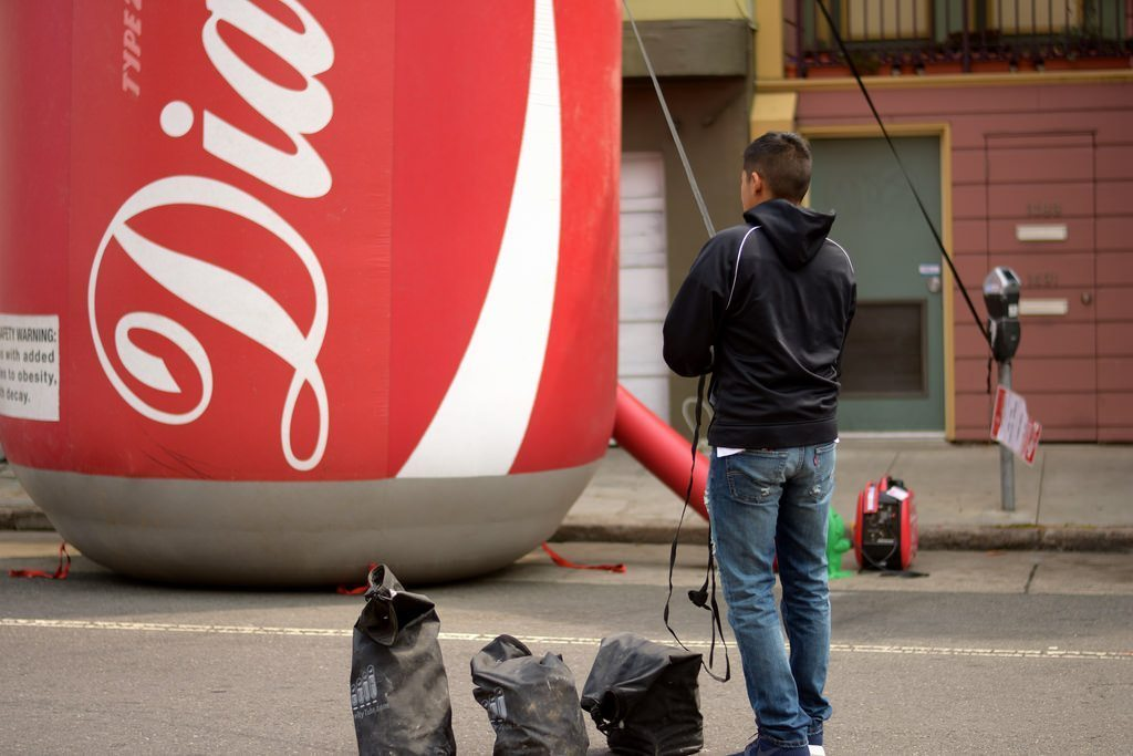 Image: A man standing by a giant can of soda labeled Diabetes
