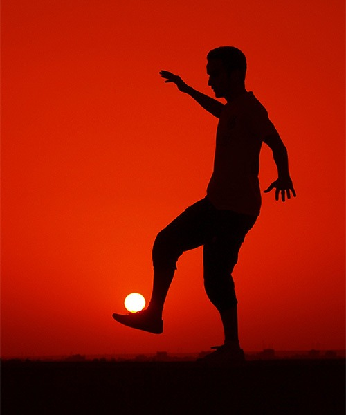 Image: A picture that looks like a man is playing soccer with the sun
