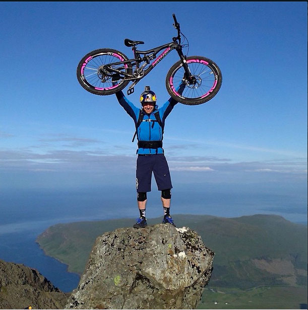 Image: Danny MaCaskill holding bike over head at the top of Cullen Ridge