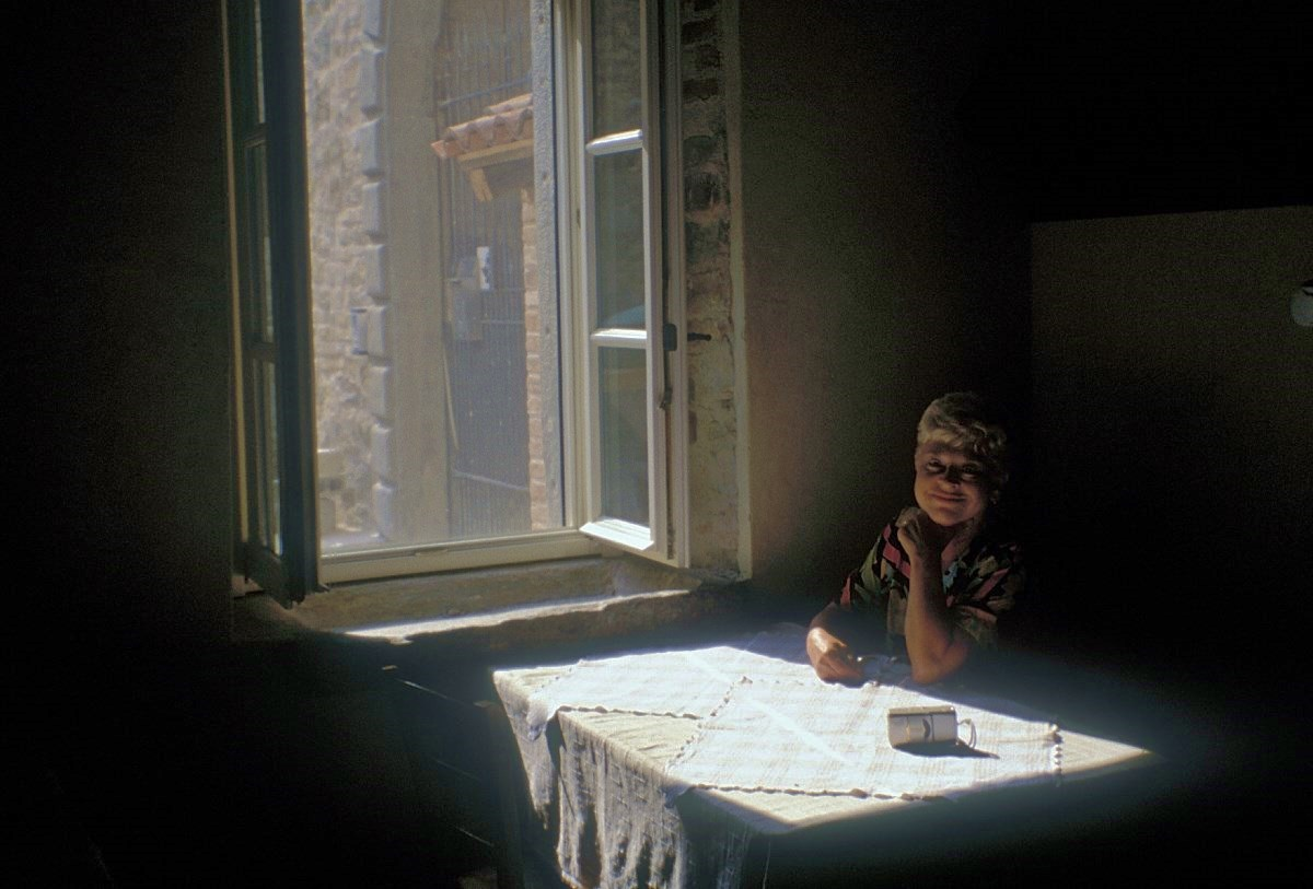 Image: Woman sitting in the shadows