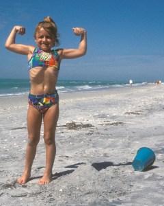 Image: Little girl in hero pose on beach