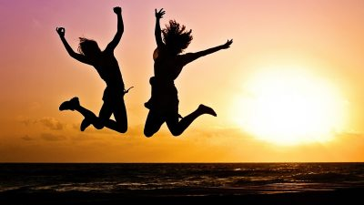 Image: Two young people jumping in the air in front of a sunset