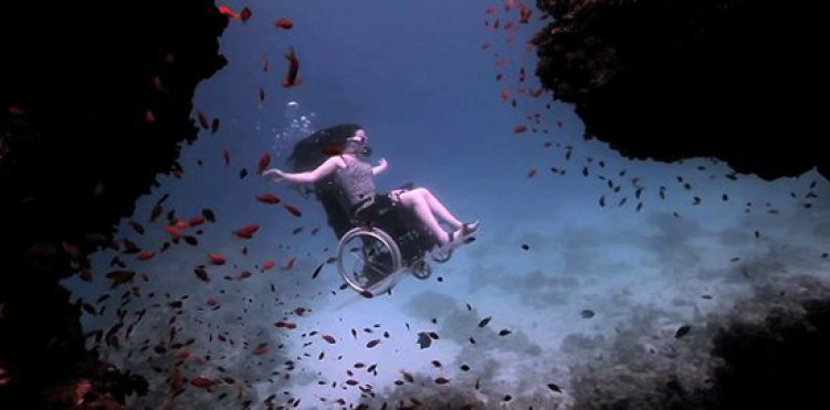 Image: Sue Austin Underwater in her wheelchair surrounded by hundreds of small red/orange fish