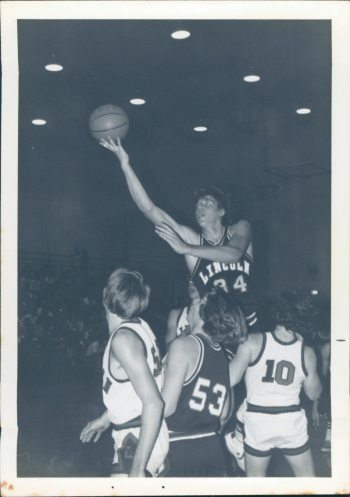 Image: Black and White photo of Dr. Chuck high above the others playing High school basketball