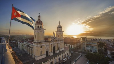 Image: Cuban flag over Plaza de la Cathdral at sunset, Santiago de Cuba, Cuba --- Image by © Corbis