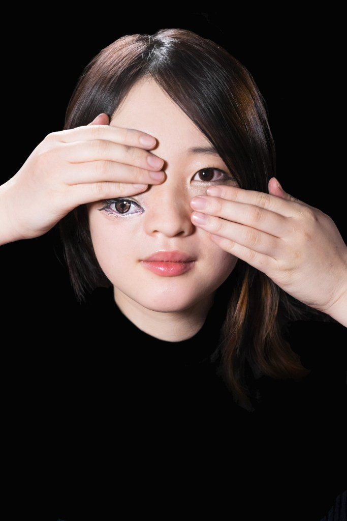 Image: Woman covering one eye with an eye on her cheek below her hand by Hikaru Cho