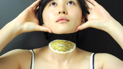 Image: looks like woman taking offer her head to reveal a grapefruit