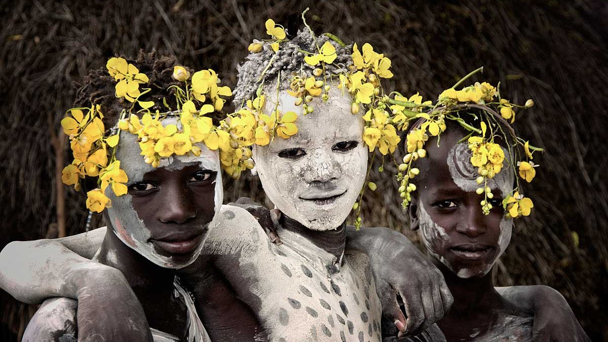 Image: Tribal girls covered with white ash, with flowers in their hair by Jimmy Nelson