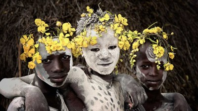 Image: Tribal girls covered with white ash, with flowers in their hair