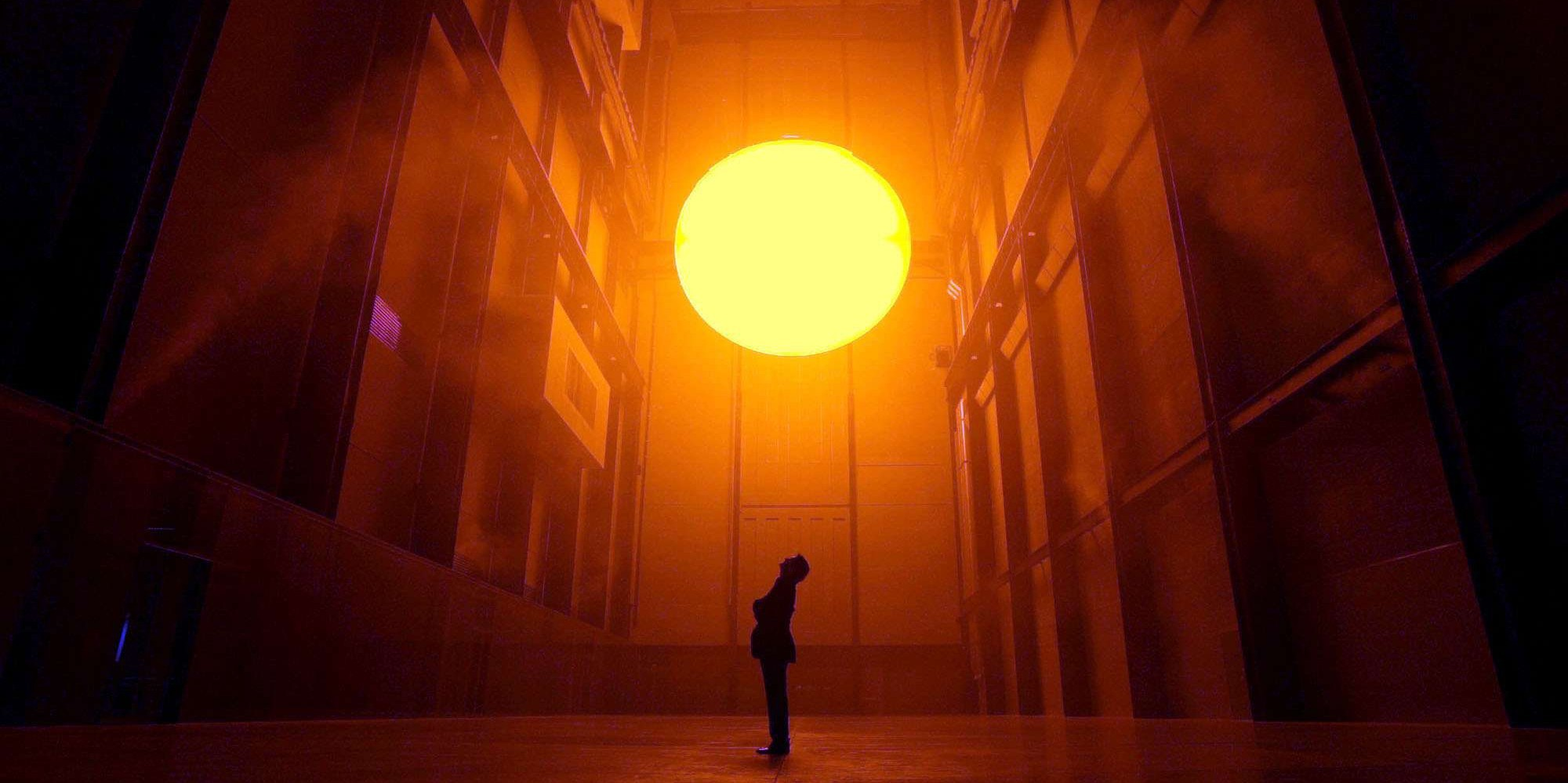 "Danish environmental sculptor Olafur Eliasson, stands in the Turbine Hall at the Tate Modern art museum in London and looks up at his art work entitled ""The Weather Project,"" in this Oct. 15, 2003 file photo. Eliasson has used mirrors, light, sound and mist to create a monochrome space that exposes and confronts the visitor."