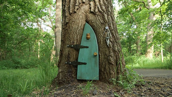 Gnome homes: the Little Owl home at the bottom of a tree with a small green door