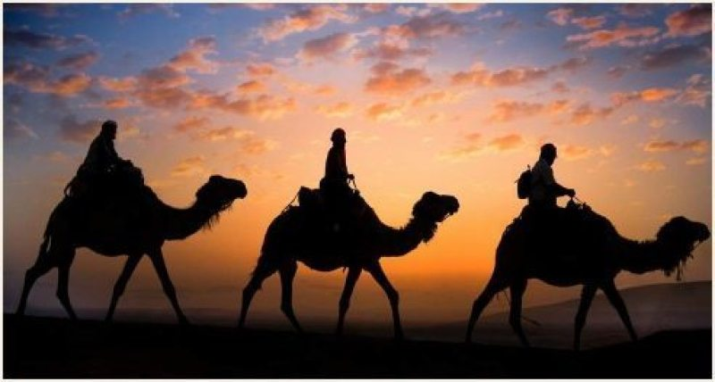 Image: Riding camels at sunset