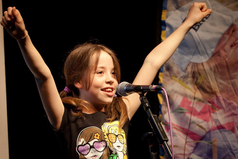 Image: Happy young girl speaking into microphone