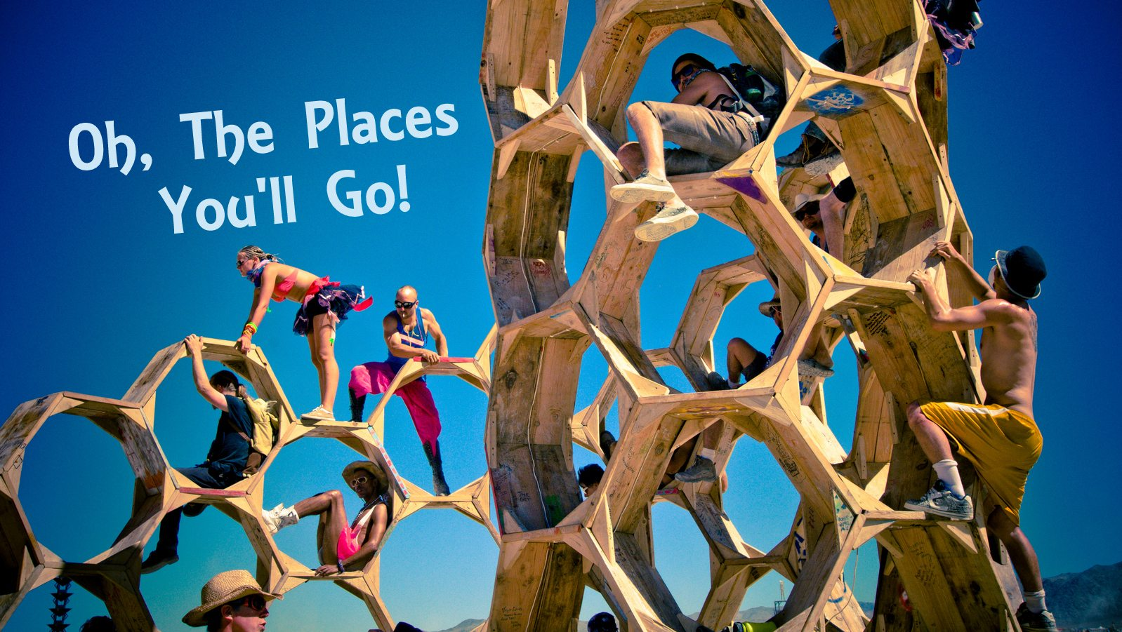 Image: Oh, The Places You'll Go burning man sculpture looking like a 3D honey comb, with many people climbing through it.