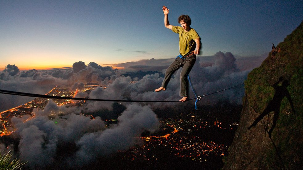 Image: A man walks a tight strip of fabric across a breathtaking valley, slacklining above the city