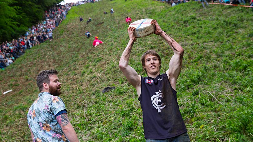 Image: Cheese Rolling Festival second race winner holding his wheel of cheese above his head