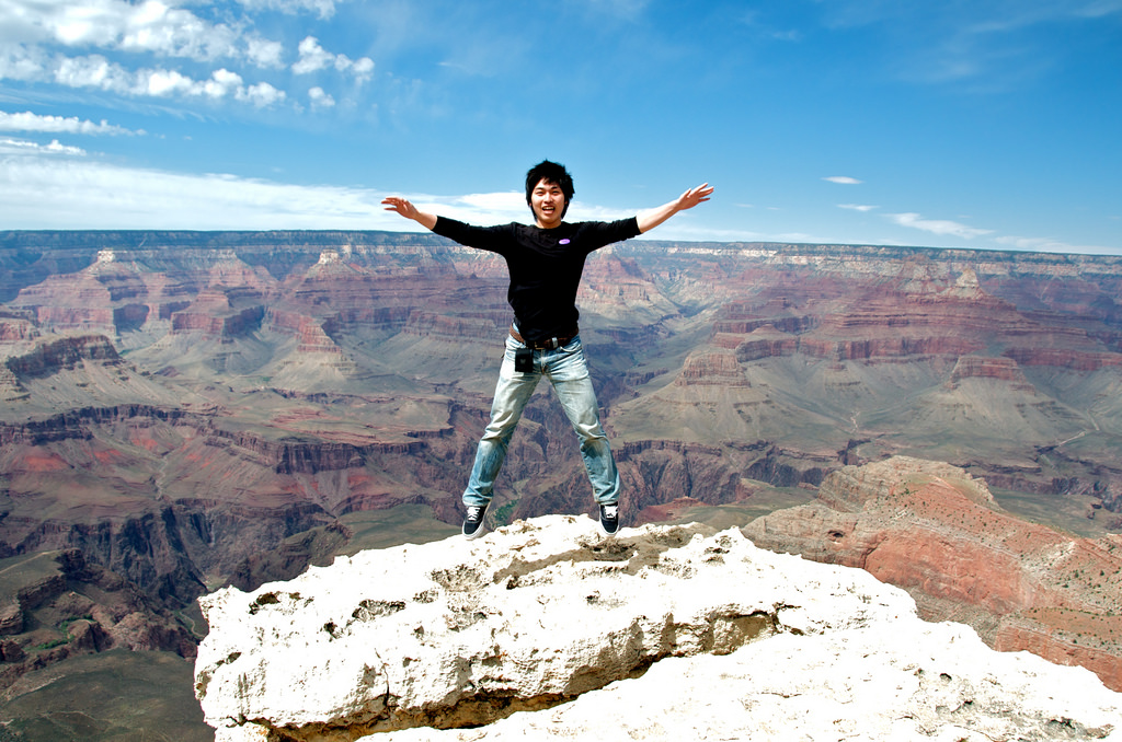 Image: Person jumping at the edge of a cliff overlooking a vast range of canyons